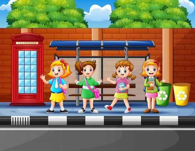 Happy school children at the bus stop