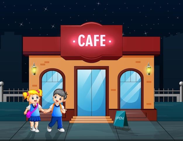 Happy school children to walk past a cafe