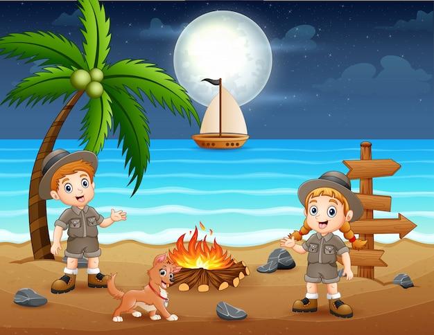 ビーチでたき火を楽しんで幸せなスカウトの子供