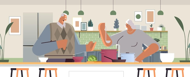 Happy senior couple preparing healthy food at home grandparents cooking together old age concept