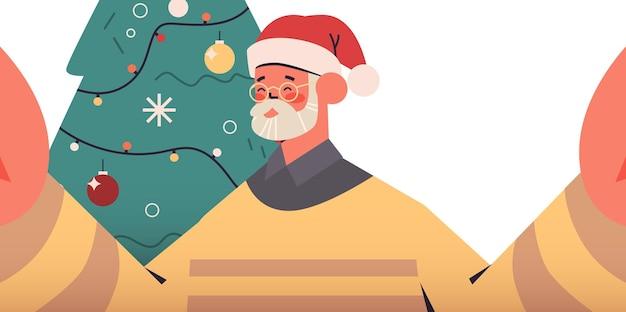 カメラを保持し、モミの木の近くでselfieを撮ってサンタ帽子で幸せな年配の男性新年クリスマス休暇お祝いコンセプト横向きの肖像画ベクトル図
