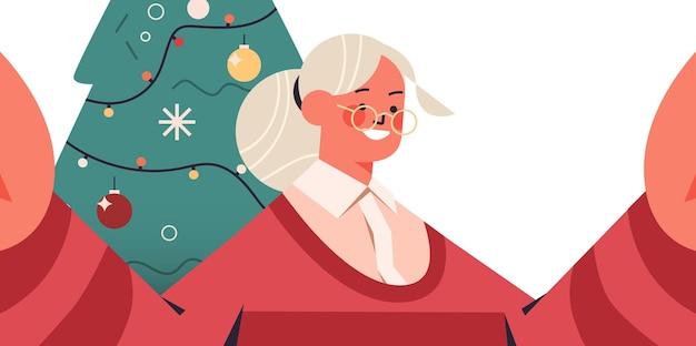 カメラを持って、モミの木の近くでselfieを撮って幸せな年配の女性新年クリスマス休暇お祝いコンセプト横向きの肖像画ベクトル図