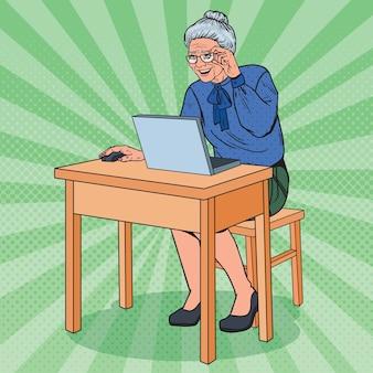 Счастливый старший женщина, используя ноутбук