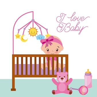 Happy sitting baby girl is in the crib with teddy rattle and bottle