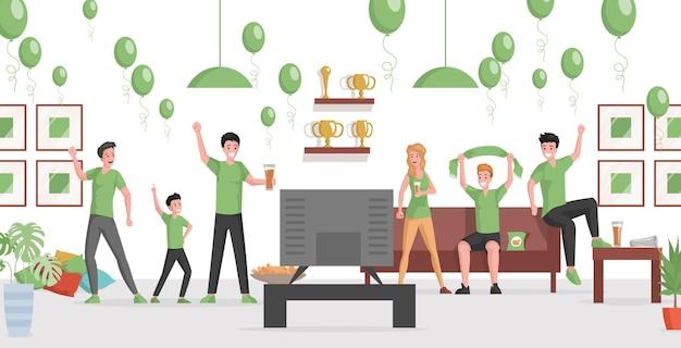 Счастливая улыбающаяся группа людей в зеленых футболках, смотрящих матч