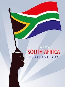 幸せな南アフリカの遺産の日、南アフリカのイラストの旗を握る手