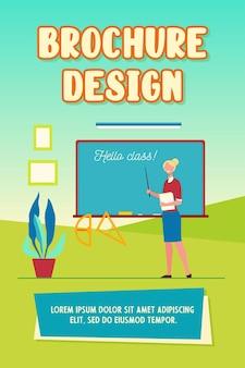 Insegnante felice che accoglie gli studenti in aula, in piedi alla lavagna con modello di brochure iscrizione hello class
