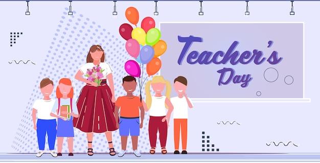 幸せな教師の日世界の休日のお祝いのコンセプト女教師と一緒に黒板近くに立っているカラフルな気球を保持している混合レース学校の子供たち