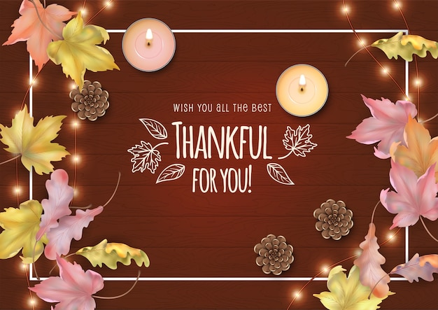 Happy thanksgiving card with fallen leaves, candles and cones on a wooden background