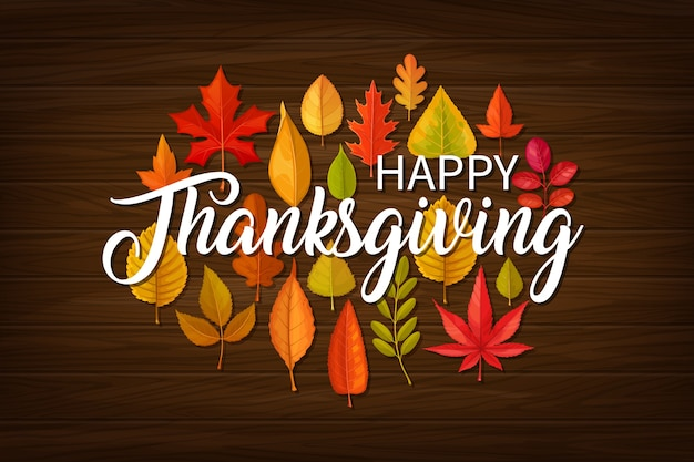 Happy thanksgiving  greeting with typography and fallen leaves of maple, oak, birch or rowan and elm on wooden background. thanks giving day fall banner, autumn season holiday, tree foliage