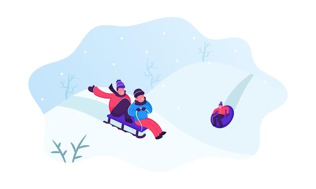 눈 언덕이있는 아름다운 눈 덮인 겨울 공원에서 썰매 타기를 즐기는 행복한 유아. 만화 평면 그림