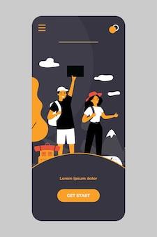 幸せな観光客のカップルがモバイルアプリで道路をヒッチハイク