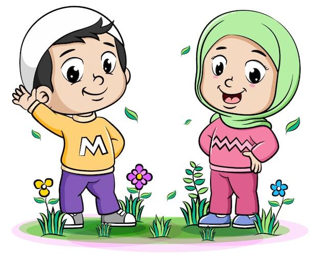 こんにちはポーズで幸せな2つのイスラム教徒の子供たち