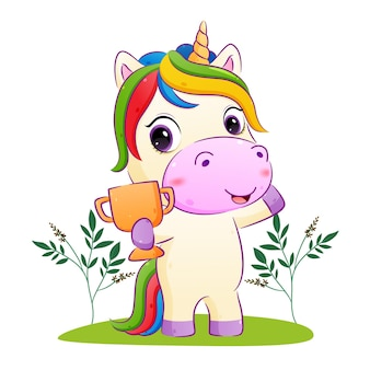 The happy unicorn is holding a golden trophy   illustration
