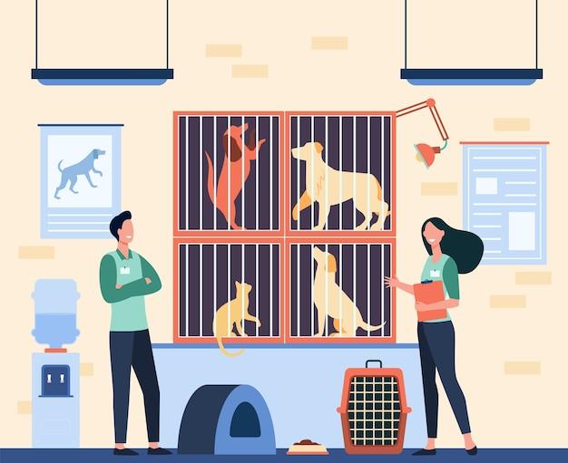 동물 보호소에서 일하는 배지를 가진 행복한 자원 봉사자들은 우리에있는 노숙자 고양이와 개를 돌보고 있습니다. 애완 동물, 동물 관리 개념을 채택하기위한 벡터 일러스트 레이션
