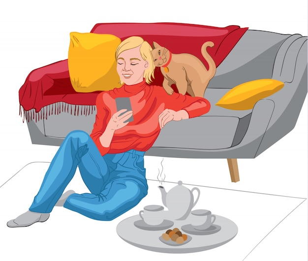 Happy woman dressed in red sweater and jeans looking in her phone while sitting on the floor and leaning on the sofa. teapot, tea cups and biscuits on a plate. cat with red collar