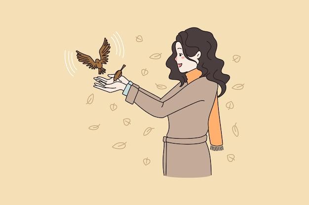 幸せな女性は屋外で鳥と遊ぶ
