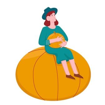 호박을 들고 큰 호박에 앉아 행복한 여자