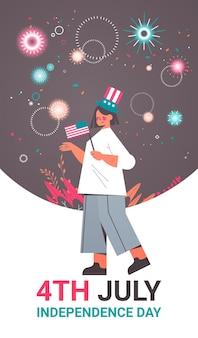 アメリカの独立記念日の休日を祝う米国旗を保持している幸せな女性、7月の垂直バナーの4日