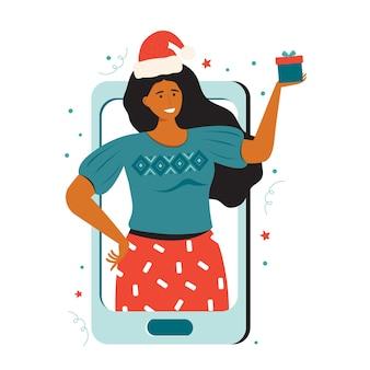 サンタの帽子をかぶった幸せな女性は贈り物を持っています