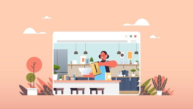 幸せな女のwebブラウザーウィンドウオンライン料理コンセプトモダンなキッチンインテリア水平肖像画で食品を準備します。