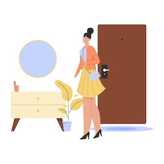 행복한 여자는 직장에서 집으로 돌아오고 아늑한 복도 장면에 서 있습니다.