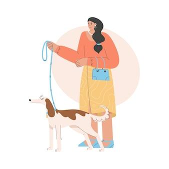 강아지와 함께 서 있고 가죽 끈을 들고 행복 한 여자입니다.