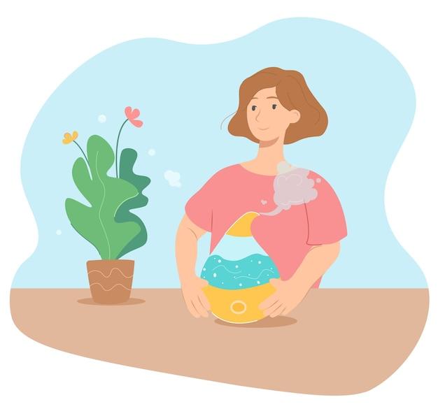Счастливая женщина с устройством увлажнителя воздуха возле цветущего растения. устройство увлажняет воздух и улучшает микроклимат в помещении, удаляет сухой воздух и помогает растениям лучше расти и иметь хорошее настроение.