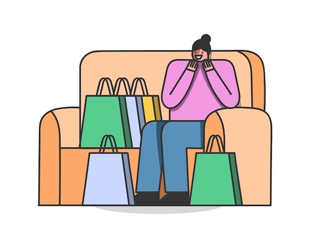コーチに座っている買い物袋と幸せな女性