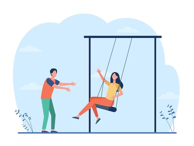 遊び場で楽しんで幸せな若いカップル。スイングでガールフレンドをスイングする男