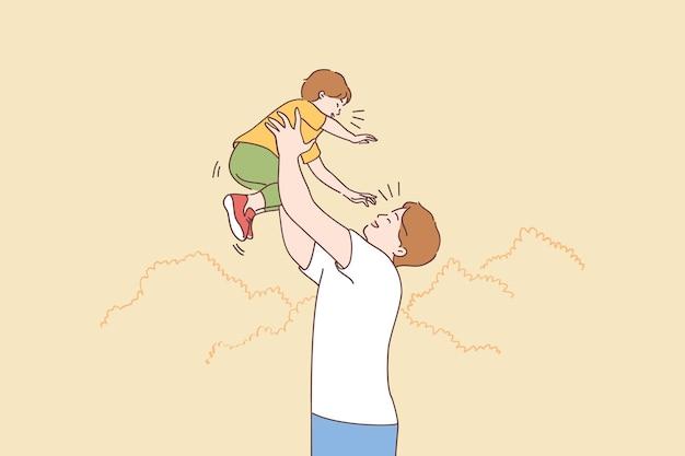 夏の自然の上を歩いている間、上げられた手で息子を運ぶ幸せな若いお父さん、休暇で一緒に時間を過ごす家族