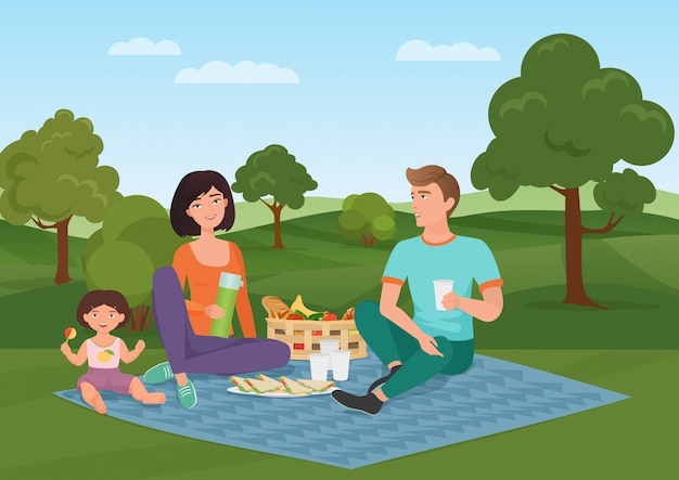 Happy young family with kid on a picnic. dad, mom and daughter are resting in nature.