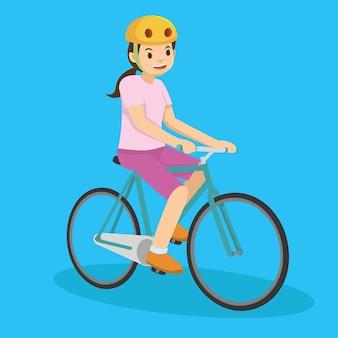 自転車に乗っているピンクの幸せな若い女の子