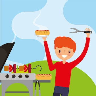 Happy young man holding fork and hotdog with kebab on grill