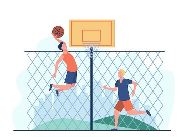 コートでバスケットボールをしている幸せな若い男性。フェンスでトレーニングし、バスケットにボールを投げる2人のチームプレーヤー。