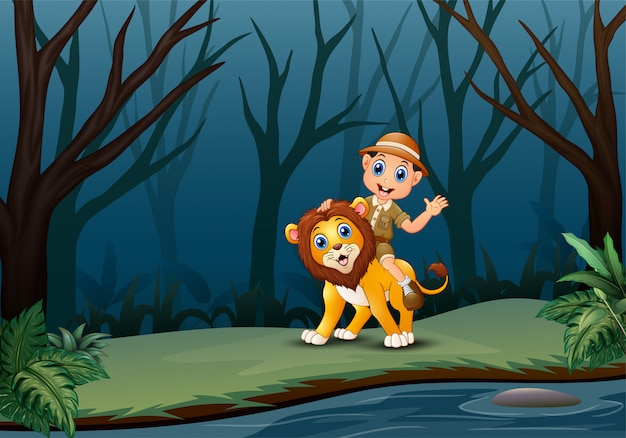 Happy zookeeper boy and lion in a forest