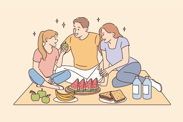 가족 개념으로 피크닉과 여가 시간을 가집니다. 피크닉 벡터 일러스트 레이 션을 가지고 과일을 먹고 함께 앉아 웃는 행복한 가족 아버지 어머니 딸