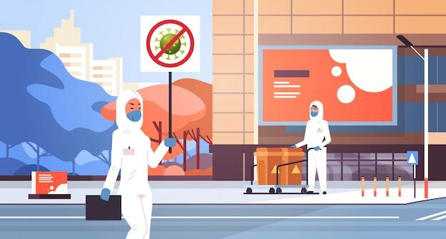 Ученые в костюмах hazmat держат остановку коронавирусный баннер дезинфекция эпидемический вирус пустой город улица wuhan пандемия риск для здоровья городской пейзаж полная длина