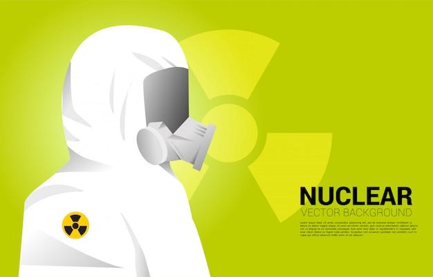 Белый костюм hazmat с полной маской и ядерным фоном. концепция радиоактивной опасности и ситуации с ядерной защитой