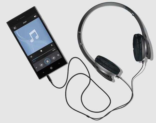 電話に接続されたヘッドフォン。プレーヤー付きのスマートフォン。