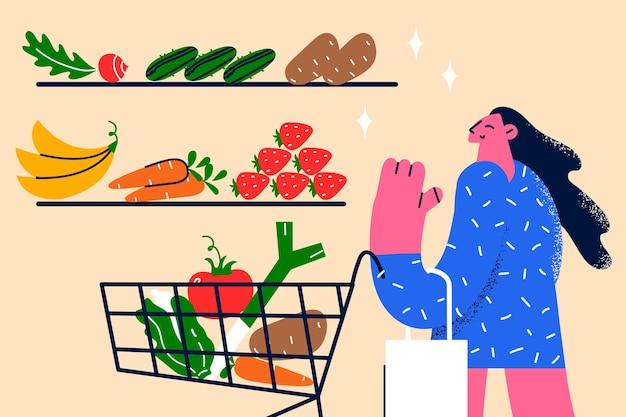 健康的なライフスタイルときれいな食事のコンセプト。健康的な食事のベクトル図の新鮮な食材を選択して食料品店に立っている若い笑顔の女性