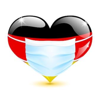 코로나바이러스로부터 보호하기 위한 의료 마스크로 독일 국기의 심장 색깔