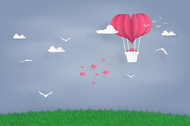 Воздушные шары формы сердца, пролетая над травой и небом. оригами бумажное искусство