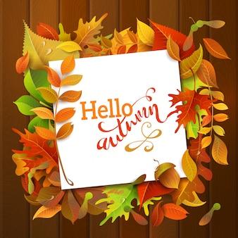 こんにちは、秋の背景。明るくカラフルな秋の白樺、ニレ、オーク、ナナカマド、メープル、栗、アスペンの葉、ウッドの背景のドングリ。紙の白い正方形のシート