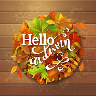 Hello autumn background. bright colourful autumn leaves on wooden background