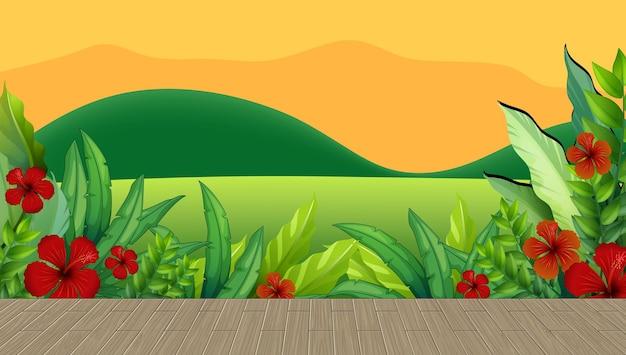 日没時に山を背景にハイビスカスの花と葉