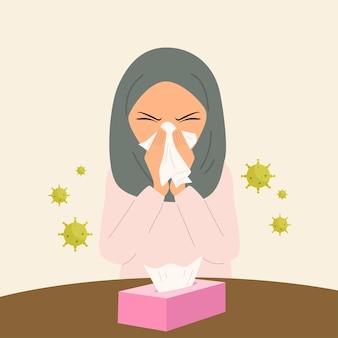 ティッシュで鼻を覆っている間にインフルエンザがくしゃみをしているヒジャーブの女性