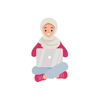 座ってラップトップを使用しているヒジャーブの女性。