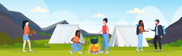 Hikers group having fun preparing food in bowler boiling pot at campfire hiking concept mix race travelers on hike tent camping campsite landscape background flat horizontal