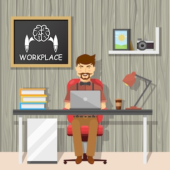 Hipster at workplace design with cheerful man behind desk and chalkboard on textural grey wall